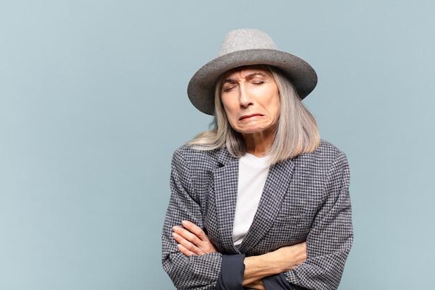 Kobieta w średnim wieku czuje się niespokojna, chora, chora i nieszczęśliwa, cierpi na bolesny ból brzucha lub grypę