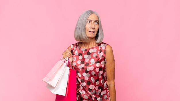 Kobieta w średnim wieku czuje się smutna, zdenerwowana lub zła i patrzy w bok z negatywnym nastawieniem, marszcząc brwi w niezgodzie z torbami na zakupy