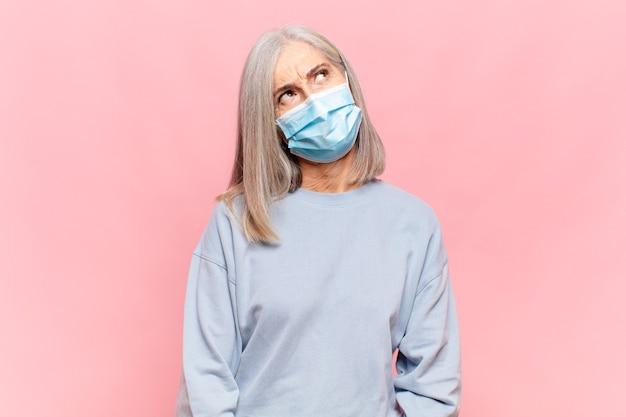 Kobieta w średnim wieku czuje się smutna, zdenerwowana lub zła i patrzy w bok z negatywnym nastawieniem, marszcząc brwi w niezgodzie