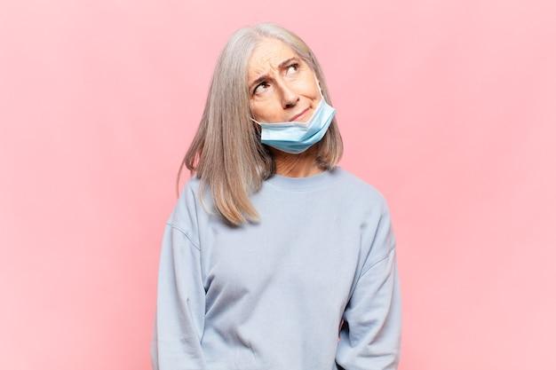 Kobieta w średnim wieku czuje się smutna, zdenerwowana lub zła i patrzy w bok z negatywnym nastawieniem, marszczy brwi w niezgodzie