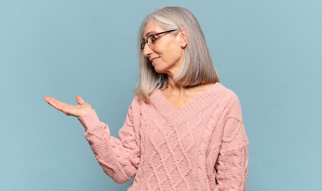 Kobieta w średnim wieku czuje się szczęśliwa i uśmiecha się niedbale, patrząc na przedmiot lub koncepcję trzymaną w dłoni na boku