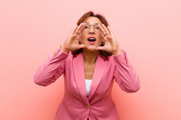 Kobieta w średnim wieku czuje się szczęśliwa, podekscytowana i pozytywna, głośno krzyczy rękami przy ustach i woła różową ścianę