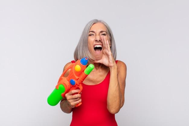 Kobieta w średnim wieku czuje się szczęśliwa, podekscytowana i pozytywna, wydając wielki okrzyk z rękami przy ustach, wołając pistoletem na wodę