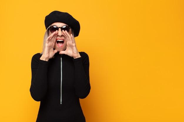 Kobieta w średnim wieku czuje się szczęśliwa, podekscytowana i pozytywna, wydając wielki okrzyk z rękami przy ustach, wołając