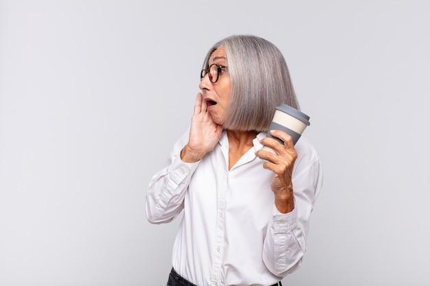 Kobieta w średnim wieku czuje się szczęśliwa, podekscytowana i zaskoczona, patrząc w bok obiema rękami na koncepcji kawy na twarzy