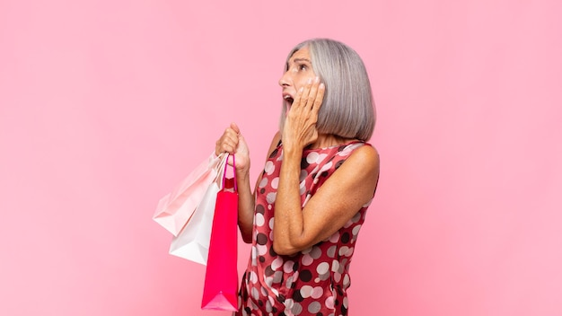 Kobieta w średnim wieku czuje się szczęśliwa, podekscytowana i zaskoczona, patrząc w bok z obiema rękami na twarzy z torbami na zakupy