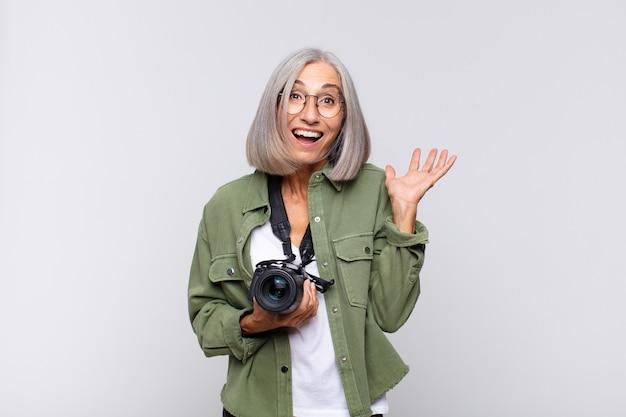 Kobieta w średnim wieku czuje się szczęśliwa, podekscytowana, zaskoczona lub zszokowana, uśmiechnięta i zdumiona czymś niewiarygodnym. koncepcja fotografa