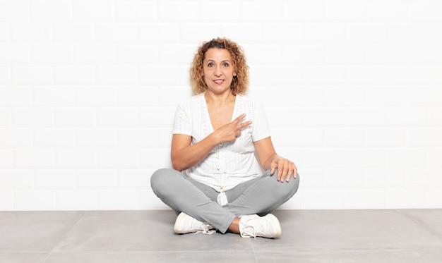 Kobieta w średnim wieku czuje się szczęśliwa, pozytywna i odnosząca sukcesy, z ręką tworzącą kształt litery v nad klatką piersiową, pokazując zwycięstwo lub pokój