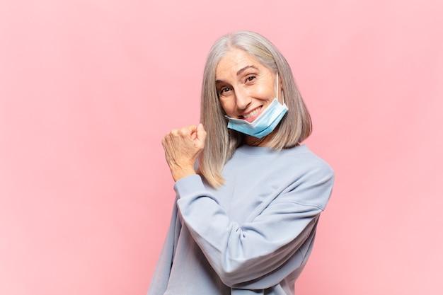 Kobieta w średnim wieku czuje się szczęśliwa, pozytywna i odnosząca sukcesy, zmotywowana do podjęcia wyzwania lub świętująca dobre wyniki