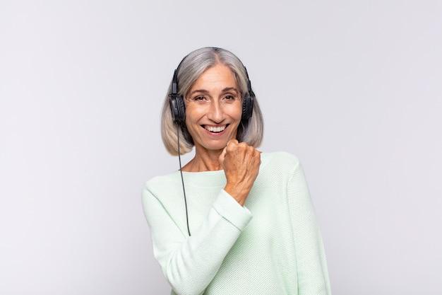 Kobieta w średnim wieku czuje się szczęśliwa, pozytywna i odnosząca sukcesy, zmotywowana, gdy staje przed wyzwaniem lub świętuje dobre wyniki. koncepcja muzyki