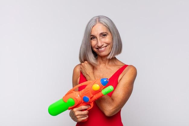 Kobieta w średnim wieku czuje się szczęśliwa, pozytywna i odnosząca sukcesy, zmotywowana, gdy staje przed wyzwaniem lub świętuje dobre wyniki z pistoletu na wodę