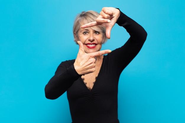 Kobieta w średnim wieku czuje się szczęśliwa, przyjazna i pozytywna, uśmiecha się i robi rękami portret lub ramkę