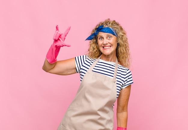 Kobieta w średnim wieku czuje się szczęśliwa, zabawna, pewna siebie, pozytywna i zbuntowana, robi rockowy lub heavy metalowy znak z koncepcją ręcznej gospodyni