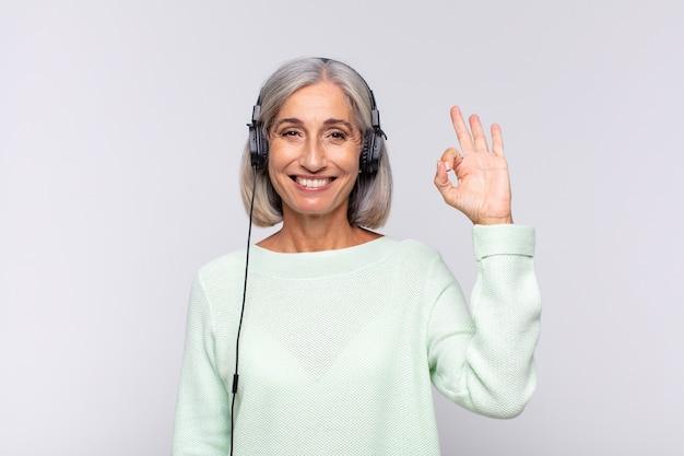 Kobieta w średnim wieku czuje się szczęśliwa, zrelaksowana i zadowolona na białym tle