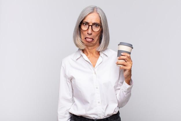 Kobieta w średnim wieku czuje się zdegustowana i zirytowana, wystawia język, nie lubi czegoś paskudnego i obrzydliwej kawy