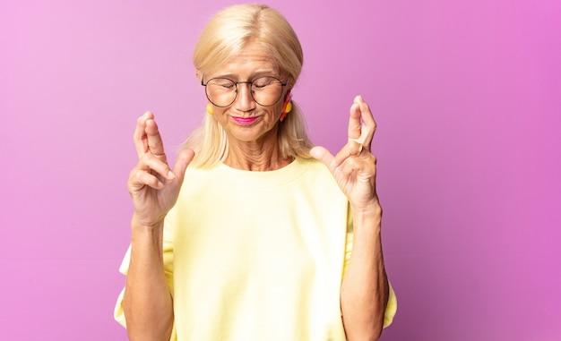 Kobieta w średnim wieku czuje się zdenerwowana i pełna nadziei, krzyżuje palce