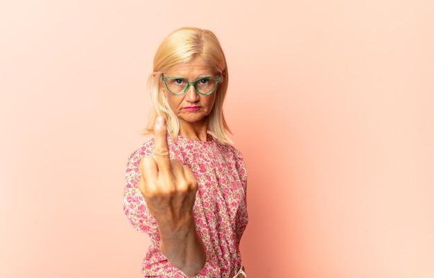 Kobieta w średnim wieku czuje się zdezorientowana i zdezorientowana, pokazując, że jesteś szalony, szalony lub oszalały