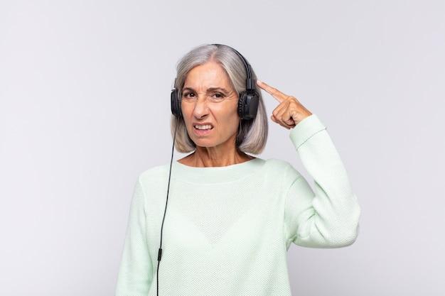 Kobieta w średnim wieku czuje się zdezorientowana i zdziwiona, pokazując, że jesteś szalony, szalony lub oszalały. koncepcja muzyki