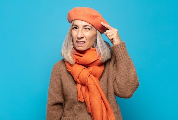 Kobieta w średnim wieku czuje się zdezorientowana i zdziwiona, pokazując, że jesteś szalony, szalony lub oszalały