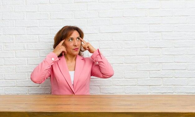 Kobieta w średnim wieku czuje się zdezorientowana lub wątpiąca, koncentruje się na pomyśle, ciężko myśli, chce skopiować miejsce na boku