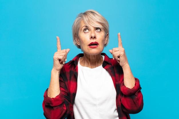 Kobieta w średnim wieku czuje się zdumiona i z otwartymi ustami, skierowaną w górę, ze zszokowanym i zaskoczonym spojrzeniem