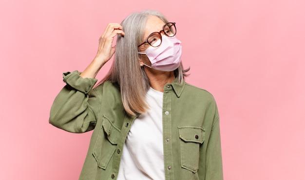 Kobieta w średnim wieku czuje się zdziwiona i zdezorientowana, drapiąc się po głowie i spoglądając w bok