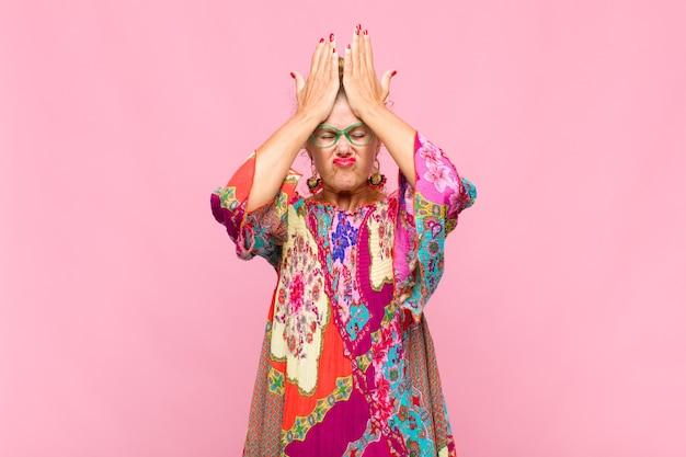 Kobieta w średnim wieku czuje się zestresowana i niespokojna, przygnębiona i sfrustrowana bólem głowy, podnosząca obie ręce do głowy