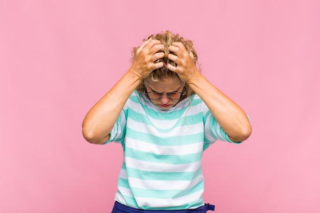 Kobieta w średnim wieku czuje się zestresowana i sfrustrowana, podnosi ręce do głowy, czuje się zmęczona, nieszczęśliwa i ma migrenę