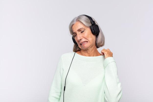 Kobieta w średnim wieku czuje się zestresowana, niespokojna, zmęczona i sfrustrowana, ciągnie za szyję koszuli, wygląda na sfrustrowaną problemem. koncepcja muzyki