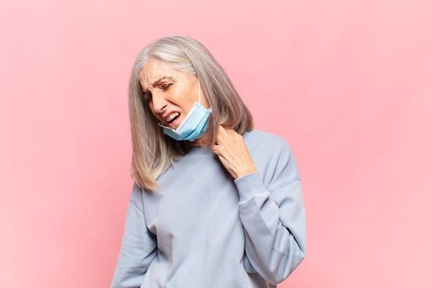 Kobieta w średnim wieku czuje się zestresowana, niespokojna, zmęczona i sfrustrowana, ciągnie za szyję koszuli, wygląda na sfrustrowaną problemem