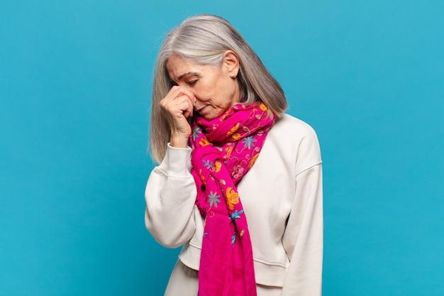 Kobieta w średnim wieku czuje się zestresowana, nieszczęśliwa i sfrustrowana, dotyka czoła i cierpi na migrenę lub silny ból głowy