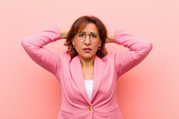 Kobieta w średnim wieku czuje się zestresowana, zmartwiona, niespokojna lub przestraszona, z rękami na głowie, panikuje na pomyłce różowa ściana