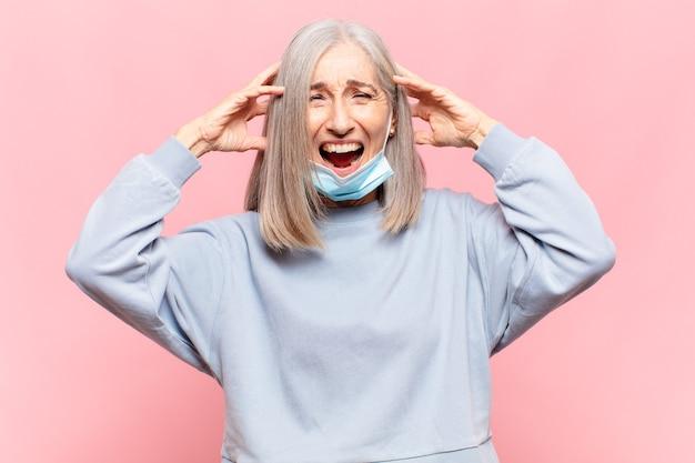 Kobieta w średnim wieku czuje się zestresowana, zmartwiona, niespokojna lub przestraszona, z rękami na głowie, panikuje podczas pomyłki