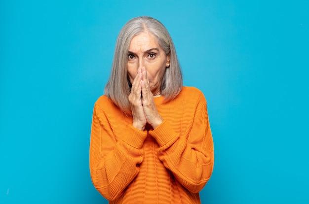 Kobieta w średnim wieku czuje się zmartwiona, zdenerwowana i przestraszona, zakrywa usta dłońmi, wygląda na zaniepokojoną i popsuła