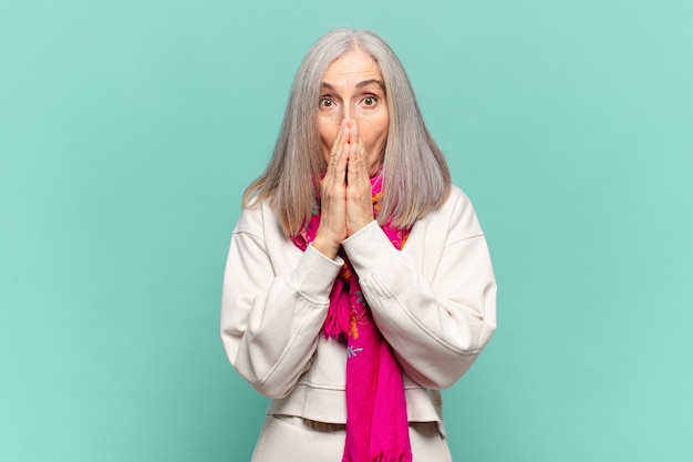 Kobieta w średnim wieku czuje się zmartwiona, zdenerwowana i przestraszona, zakrywa usta rękami, wygląda na zaniepokojoną i pomieszała się