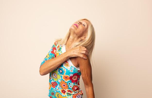 Kobieta w średnim wieku czuje się zmęczona, zestresowana, niespokojna, sfrustrowana i przygnębiona, cierpi na ból pleców lub szyi