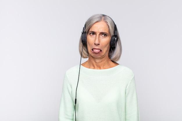 Kobieta w średnim wieku czuje się zniesmaczona i poirytowana, wystawia język, nie lubi czegoś paskudnego i obrzydliwego. koncepcja muzyki