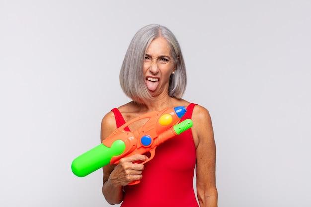 Kobieta w średnim wieku czuje się zniesmaczona i poirytowana, wystawia język, nie lubi czegoś paskudnego i obrzydliwego z pistoletem na wodę