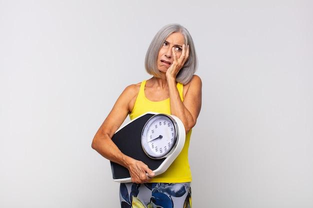 Kobieta w średnim wieku czuje się znudzona, sfrustrowana i senna po męczącym, nudnym i nudnym zadaniu, trzymając twarz ręką. koncepcja fitness