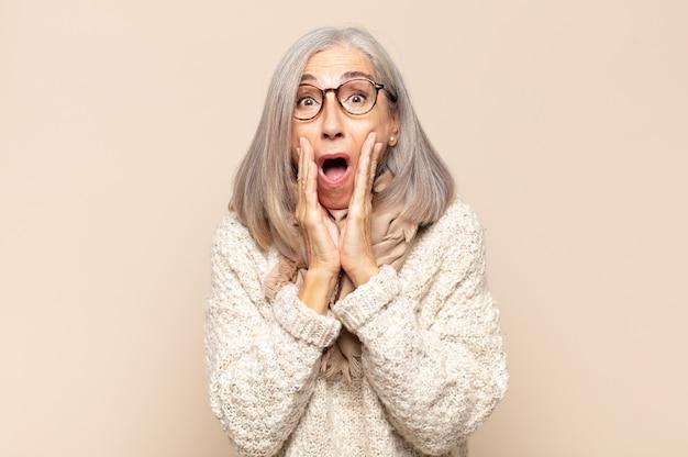 Kobieta w średnim wieku czuje się zszokowana i przestraszona, wygląda na przerażoną z otwartymi ustami i dłońmi na policzkach