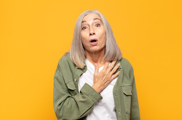 Kobieta w średnim wieku czuje się zszokowana i zaskoczona, uśmiecha się, bierze rękę do serca, jest szczęśliwa, że jest tą jedyną lub okazuje wdzięczność