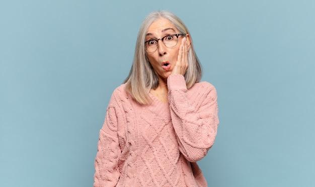 Kobieta w średnim wieku czuje się zszokowana i zdumiona, trzymając się z niedowierzaniem twarzą w twarz z szeroko otwartymi ustami
