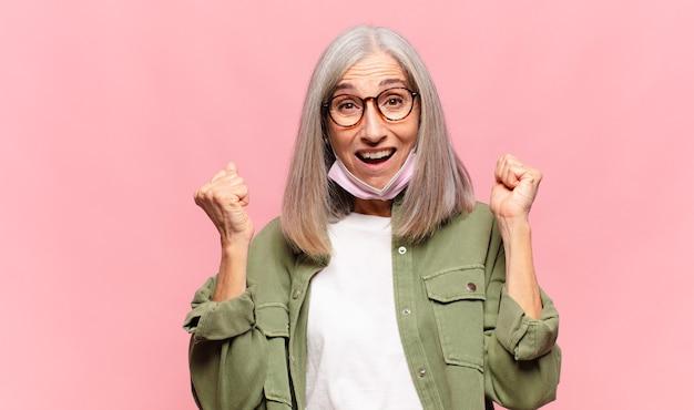 Kobieta w średnim wieku czuje się zszokowana, podekscytowana i szczęśliwa, śmiejąc się i świętując sukces, mówiąc wow