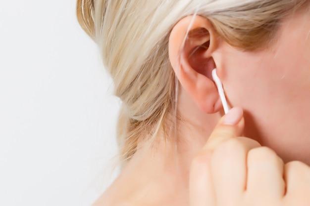 Kobieta w średnim wieku czyści ucho wacikiem lub patyczkiem. zbliżenie procedury rutynowej higieny opieki zdrowotnej w domu