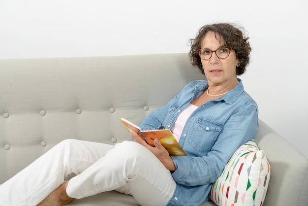 Kobieta w średnim wieku czyta, siedząc na kanapie