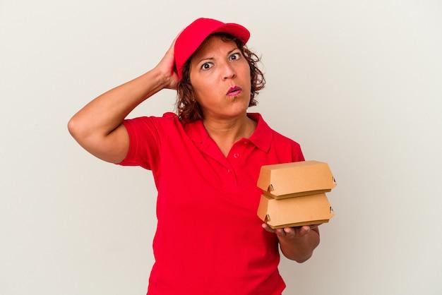 Kobieta w średnim wieku dostarczająca hamburgery na białym tle będąc w szoku, przypomniała sobie ważne spotkanie.