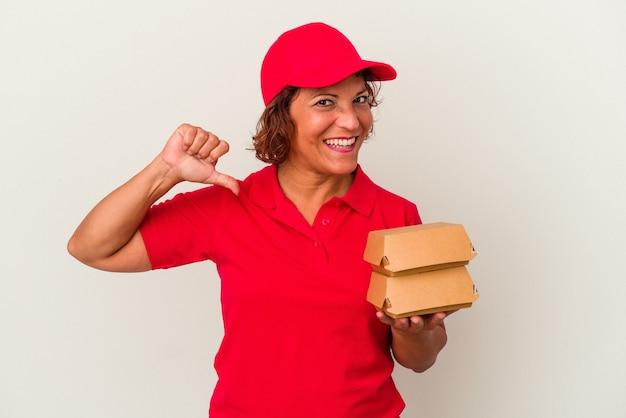 Kobieta w średnim wieku dostarczająca hamburgery na białym tle czuje się dumna i pewna siebie, przykład do naśladowania.
