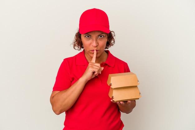 Kobieta w średnim wieku dostarczająca hamburgery na białym tle dochowując tajemnicy lub prosząc o ciszę.
