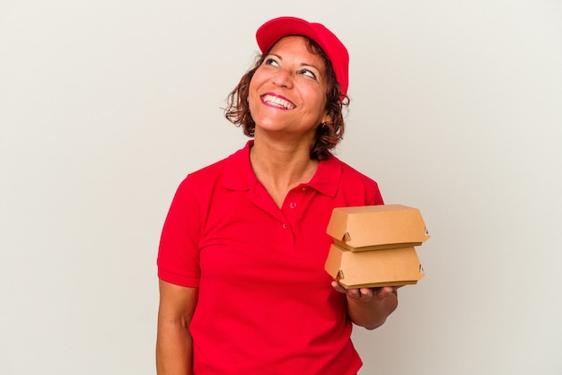 Kobieta w średnim wieku dostarczająca hamburgery na białym tle marząca o osiągnięciu celów i celów