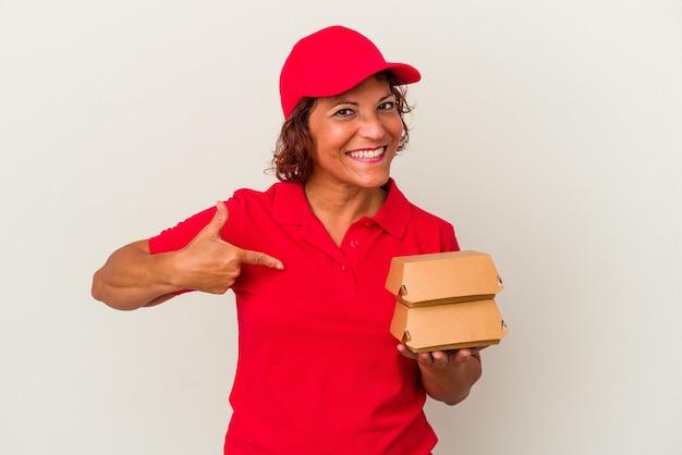 Kobieta w średnim wieku dostarczająca hamburgery na białym tle osoba wskazująca ręcznie na miejsce na koszulkę, dumna i pewna siebie